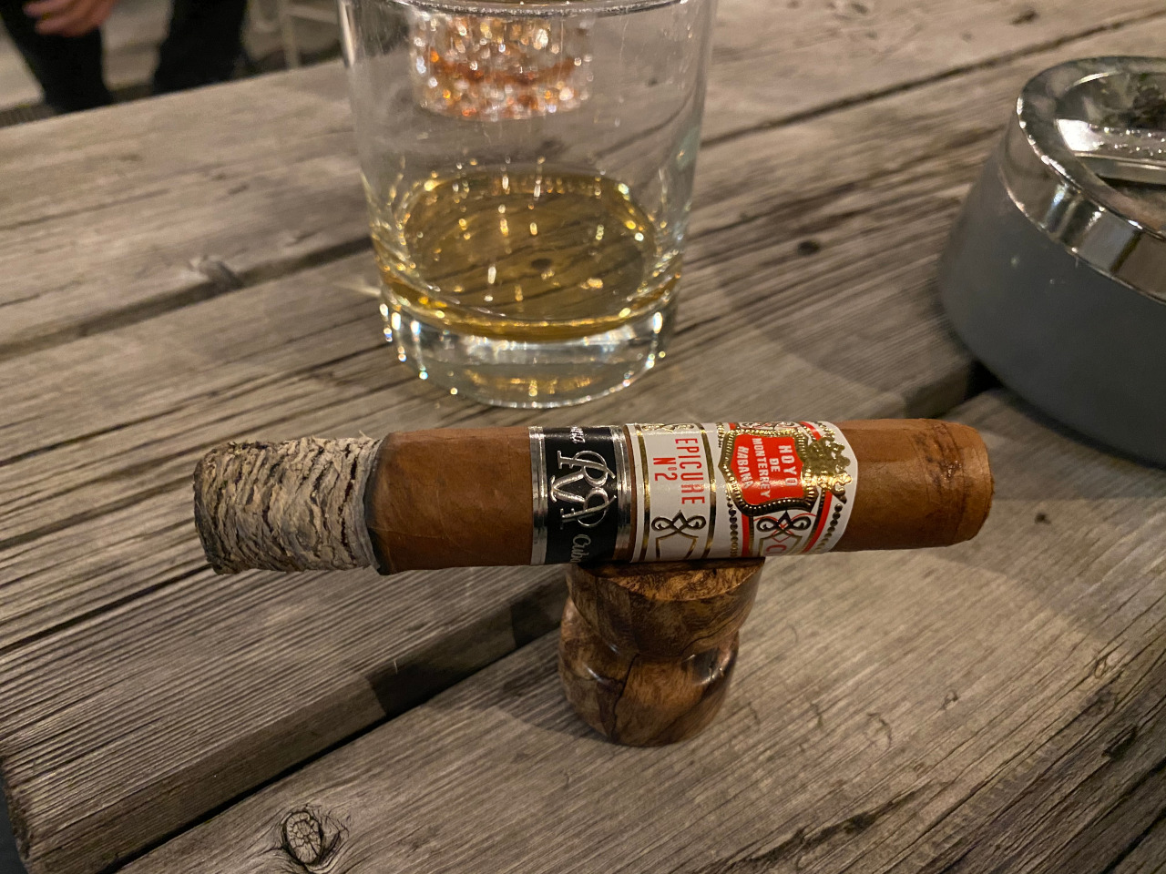 Cigar on stand in front of glass with Whiskey
