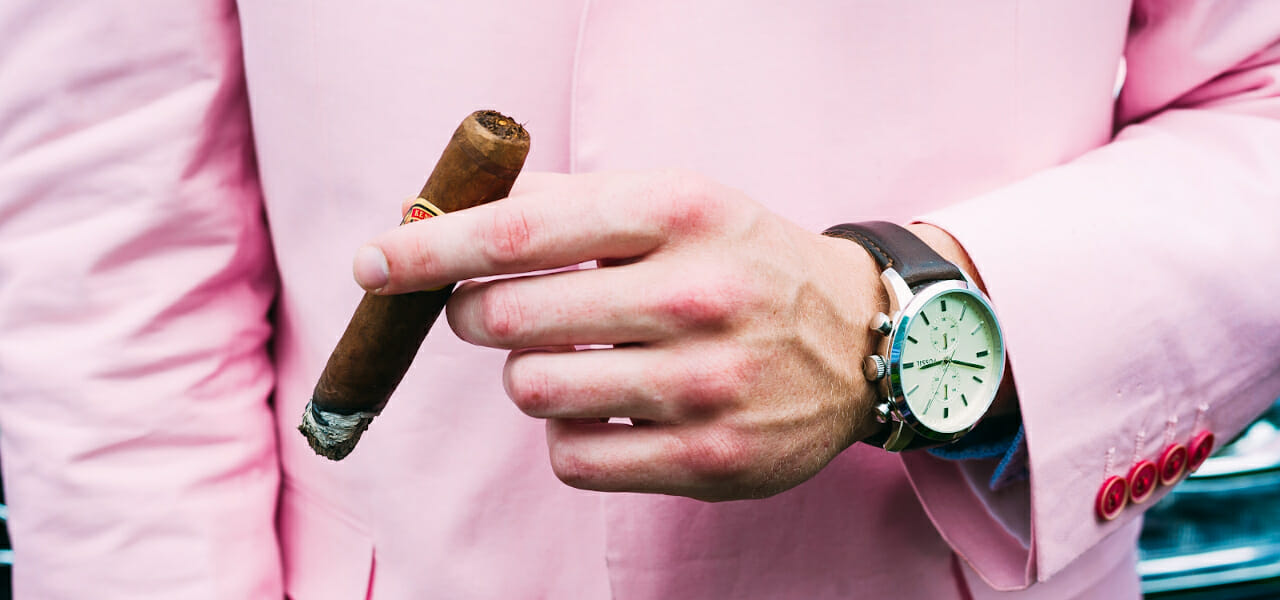 cropped image of man in pink sports jacket focus of hand holding cigar